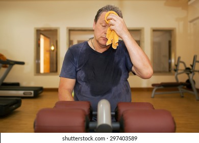 Exhausted mature man wiping sweat with a towel after intensive training in the gym