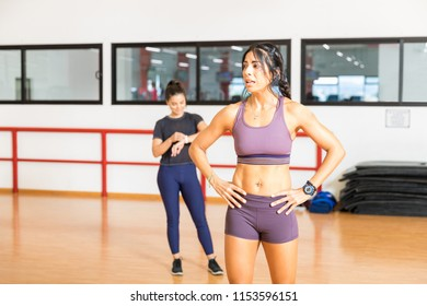Exhausted mid adult woman standing with hands on hips after exercising in a gym class