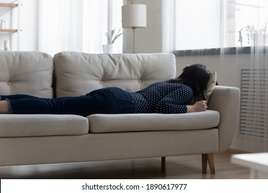 Exhausted millennial asian korean woman resting sleeping on sofa after hard working day, tired young vietnamese lady fall asleep napping on couch, fatigue overwork or sleepless night concept.