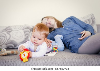 Exhausted mother and baby on the couch