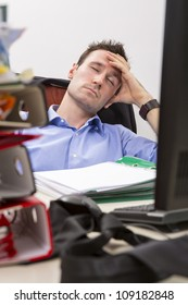 Exhausted office worker falls asleep in front of his computer, surrounded by a pile of file folders