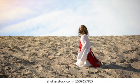 Exhausted pilgrim kneeing from exhaustion, lost in desert and life, concept