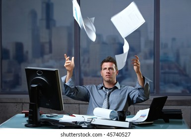 Exhausted professinal throwing documents into air sitting at office desk in overtime.