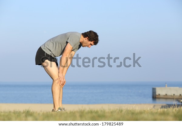 Exhausted runner man resting on the beach after workout with the ocean in the background