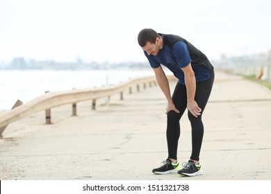 Exhausted runner resting breathing fresh air after sport