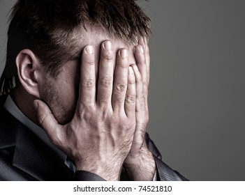 Exhausted sad businessman covering his face by hands