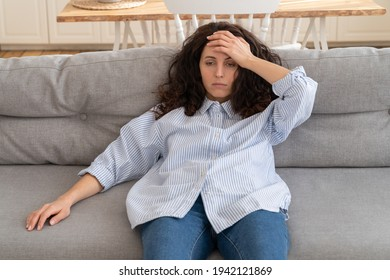 Exhausted sad woman lying on sofa at home feels tired after hard-working day, spending time alone. Stressed mother feel overwhelmed on couch at home, resting, touching her head, fatigue concept