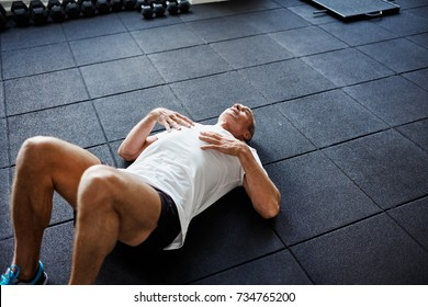 Exhausted senior man in sportswear lying alone on the floor of a gym after working out