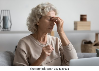 Exhausted senior older woman taking off glasses, suffering from dry eyes syndrome after computer overwork, sitting alone on sofa in living room. Middle aged grandmother rubbing eye, feeling tired.