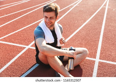 Exhausted sportsman finished running at the stadium, resting