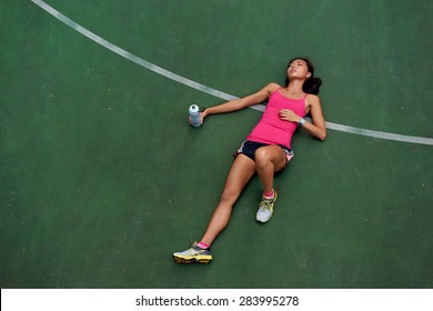 exhausted sporty woman runner laying on basketball court after fitness running workout outdoors