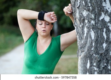 Exhausted sweaty overweight plus sized fat woman leaning on tree