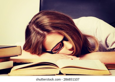 Exhausted teenage woman sleeping on the desk