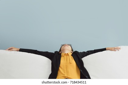 Exhausted, Tired Asian Business woman in Yellow shirt and black suit sitting on white sofa with blue wall. Stress from overtime working concept.