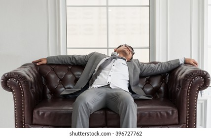 Exhausted, tired of Asian man sitting and sleeping on brown leather sofa in the white room at the office. Health care of Businessman concept.