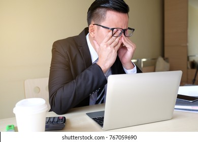 Exhausted tired businessman working on laptop at office, massaging nose bridge, holding glasses, feeling fatigue discomfort, eye strain after long wearing spectacles, eyesight problem, need eye drops