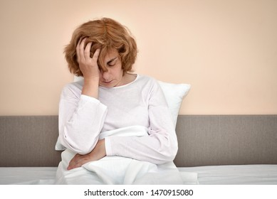 Exhausted and tired mature woman with severe headache sitting in bed and holding her head