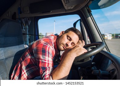Exhausted truck driver falling asleep on steering wheel. Tiredness and sleeping concept.