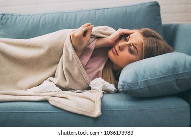 Exhausted woman having fever and checking temperature.Image is intentionally toned.