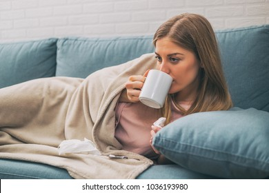 Exhausted woman having fever and she is drinking a tea.Image is intentionally toned.