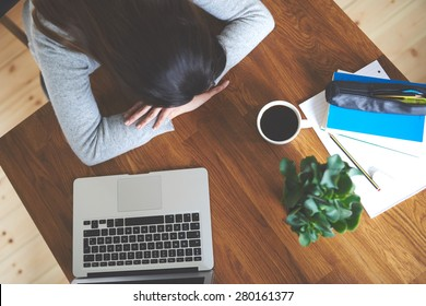 Exhausted  woman sitting at table in home office with head lying on table.