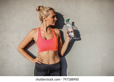 exhausted woman with water on the beach after workout