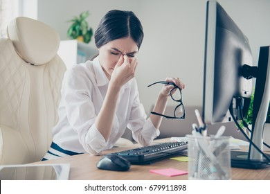 Exhausted young asian entrepreneur lawyer is holding his nose bridge with closed eyes, she is tired and depressed. She is sitting at her work place, holding eyewear