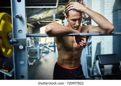 Exhausted young athlete with bare muscular torso leaning on barbell while taking short break from intensive workout at spacious gym, portrait shot
