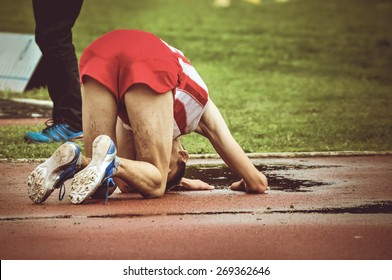 Exhausted young athlete falling on the ground after long run. Male runner on his knees on the running track after winning or loosing a race.