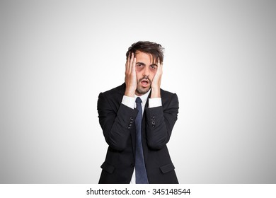 Exhausted young business man with dark eye bags, on gray background.