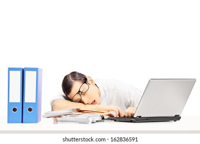 Exhausted young businessman sleeping on a desk at his workplace, isolated on white background