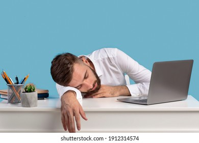 Exhausted young businessman sleeping on his desk, tired of overworking on blue studio background, copy space. Millennial workaholic suffering from chronic fatigue at office, panorama