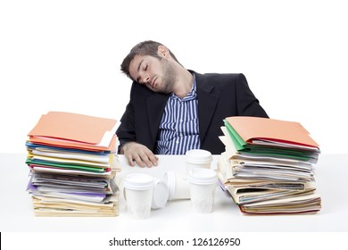 Exhausted young businessman sleeping at work