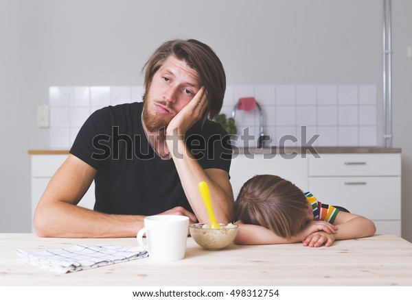exhausted young dad sitting with his kid on kitchen on early morning and trying to feed