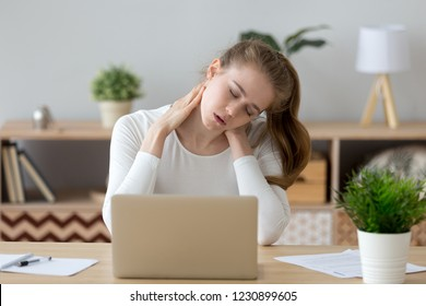 Exhausted young female sit at home office desk massaging neck feeling ache, tired girl suffer from back pain or strain, having spasm symptoms, millennial woman feel unwell from sedentary lifestyle