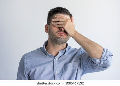 Exhausted young man with stubble covering face with hand in despair. Upset displeased businessman in blue shirt standing against gray background. Tired person concept