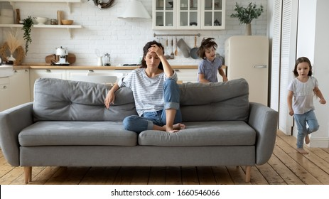 Exhausted young mum sit on couch in kitchen feel unwell tired from ill-behaved loud little children running playing, sick annoyed mother or nanny relax on sofa suffer from headache, parenting concept