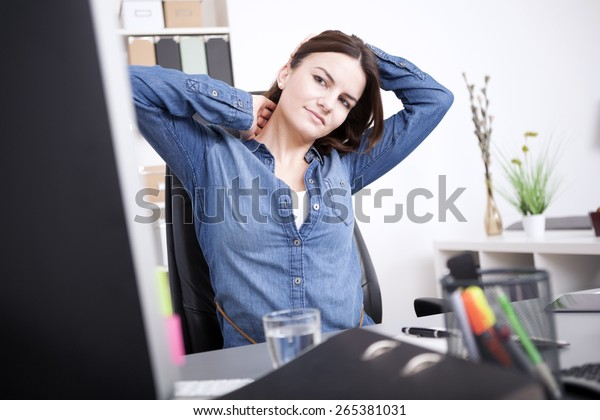 Exhausted Young Office Woman Sitting at her Office, Holding her Head and Neck While Looking at Computer Screen.