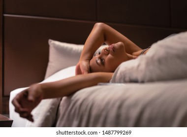Exhausted young professional woman stretched out laying on bed in deep thought - Diverse Asian millennial female resting in room at night and thinking - mental health, hotel and business trip concept
