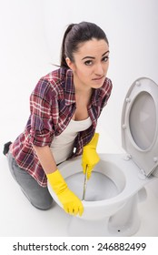 Exhausted young woman is cleaning a toilet on grey background.