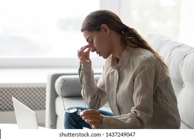 Exhausted young woman sit on couch take off glasses massage nose bridge after long hours working at computer, tired female take break from laptop feel fatigue suffer from migraine or blurry vision
