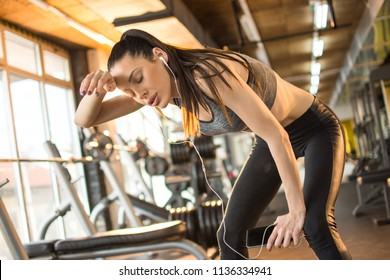 Exhausted young woman taking a break after hard workout in the gym