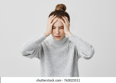Exhausted young woman touching her head with eyes closed. Female exchange worker suffering from unbearable headache. Health concept