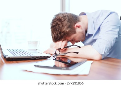 Exhausting work. Young businessman sleeping on desk covered with notebook papers and tablet in office.