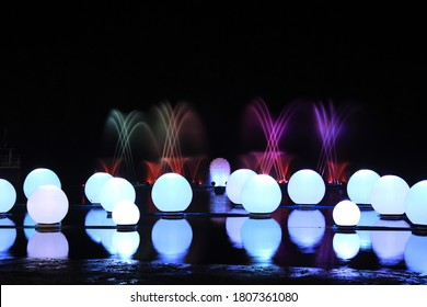 An exhibit showing water and light at night It uses colored balls and fountains behind it, and uses spotlighting techniques to enhance its beauty.