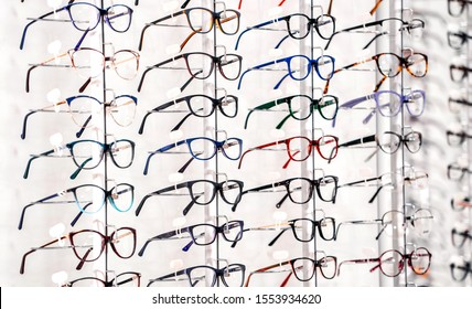 exhibition of glasses at shelves. Fashionable spectacles shown on a wall at the optical shop. Closeup. - Shutterstock ID 1553934620