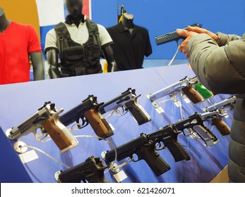Exhibition of guns, a buyer test the product.