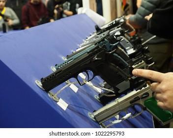 Exhibition of guns, a man's hand points to a gun.