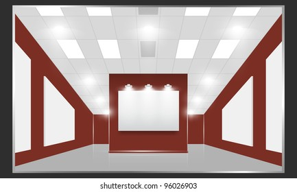 Exhibition hall with white frames on the red wall, illuminated by floodlights.