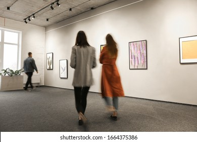 Exhibition in modern crowded art gallery